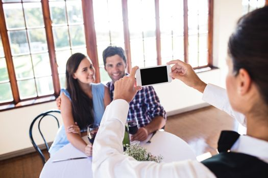 Waitress clicking photo of a couple in restaurant