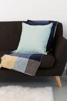 Cushions and blanket arranged on sofa