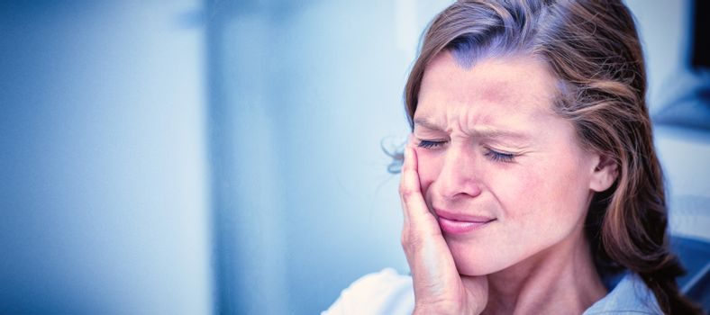 Unhappy woman having a toothache  in dental clinic