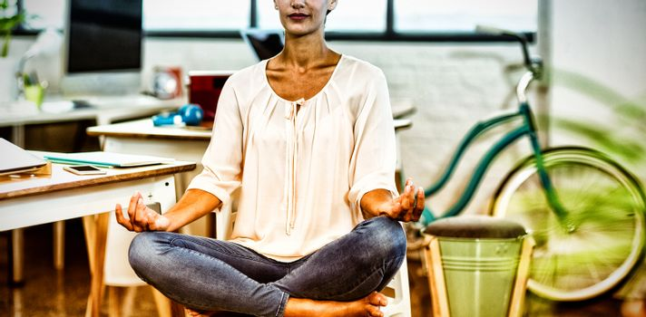 Woman sitting on chair and performing yoga in office
