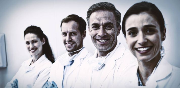 Portrait of smiling dentists standing with arms crossed in dental clinic
