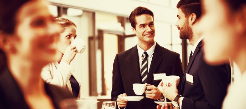 Businesspeople interacting with each other while having coffee