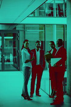 Happy businesspeople standing in office corridor