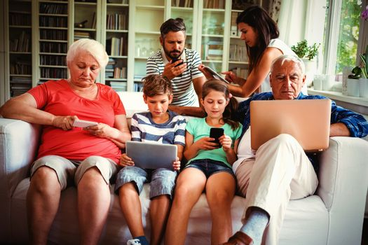 Multi-generation family sitting on sofa and using various technologies at home