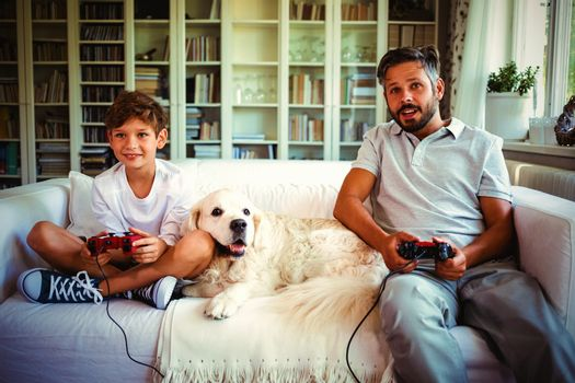 Father and son sitting on sofa with pet dog and playing video games at home