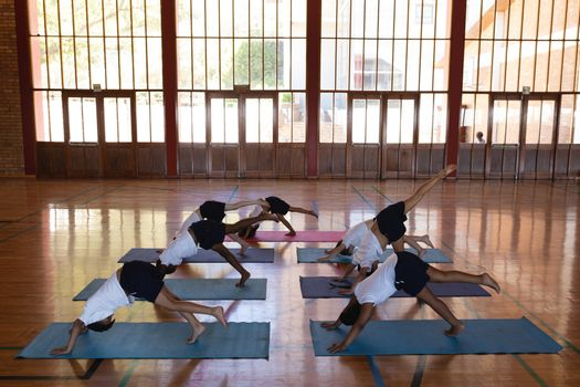 High angle view of schoolkids doing yoga position on a yoga mat in school gymnast