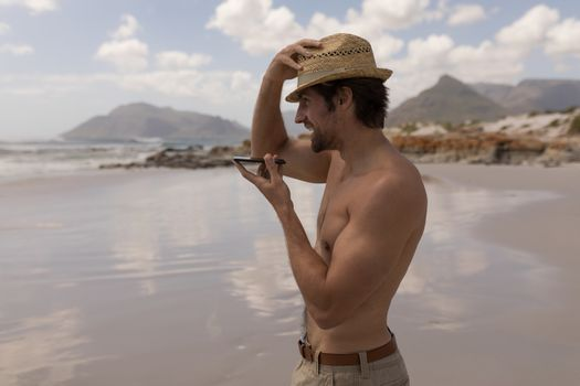 Young man holding hat and talking on mobile phone