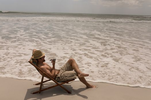 Young man with hat relaxing on sun lounger and talking on mobile phone