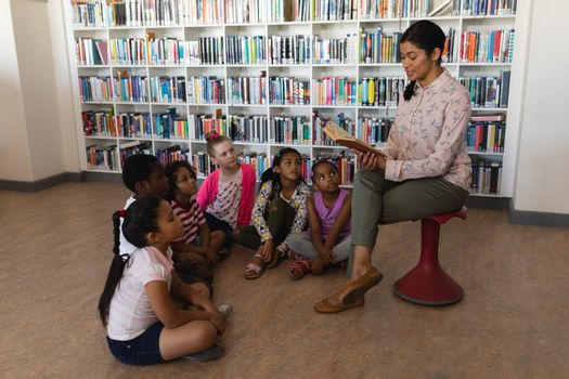 Female teacher reading a story to schoolkids