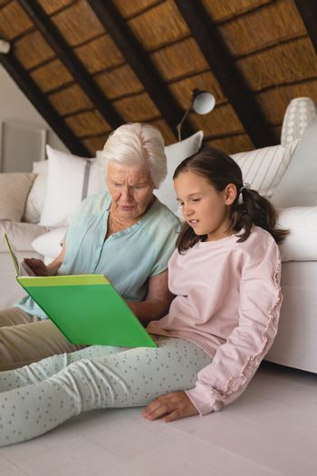Grandmother and granddaughter reading story book