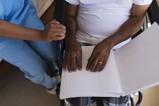 Blind senior man reading a braille at home