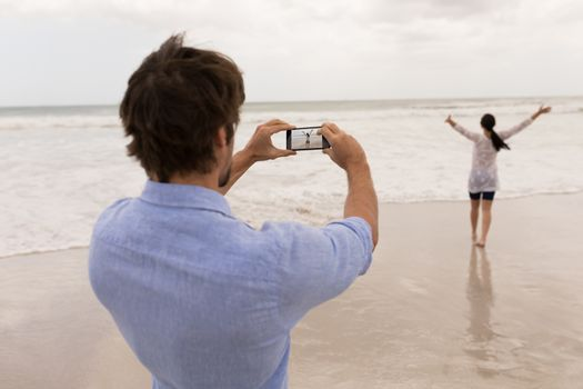 Man clicking photo of woman with mobile phone