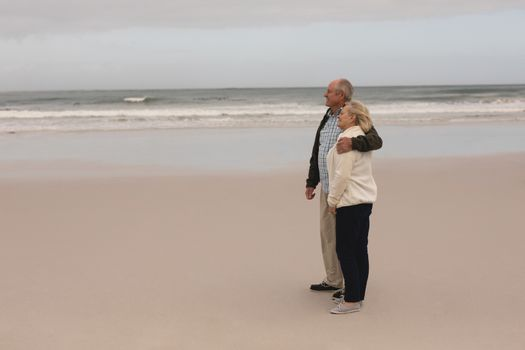Senior couple standing with arm around at the beach