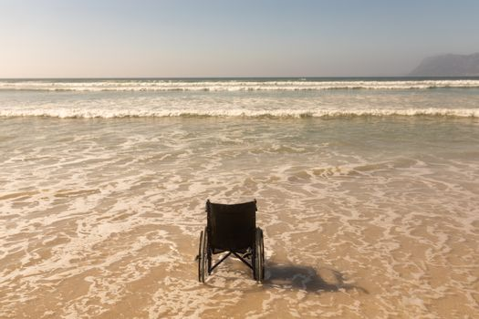 Wheelchair at seashore on the beach