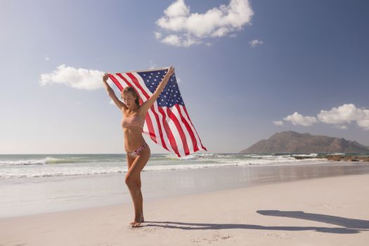 Young woman holding waving American flag at beach