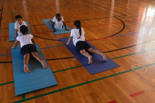 High angle view of schoolkids doing yoga on a yoga mat in school gymnasium