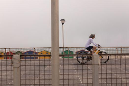 Senior woman riding bicycle on promenade