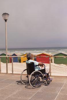 Senior man sitting on wheelchair at promenade
