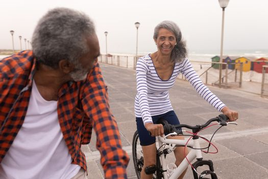 Senior couple with bicycle looking each other on promenade