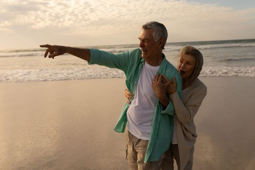 Senior man with senior woman pointing at distant on the beach