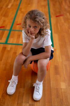 Schoolgirl sitting on basketball in basketball court