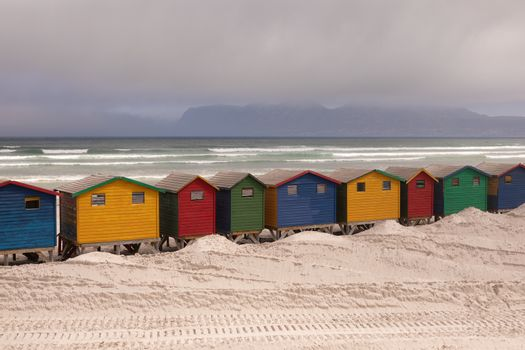 Multicoloured beach huts on beach with ocean in the background