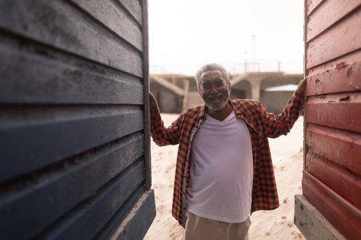 Senior man standing between beach huts