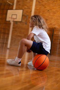 Schoolgirl sitting on basketball on basketball court