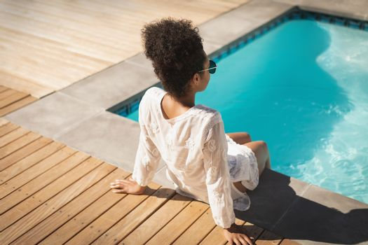Young mixed-race woman with sunglasses sitting at poolside