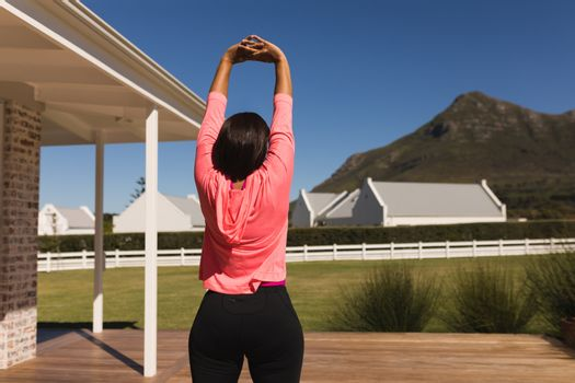 Woman stretching in the backyard of home