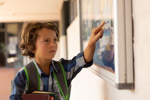 Schoolboy pointing at noticeboard in the corridor