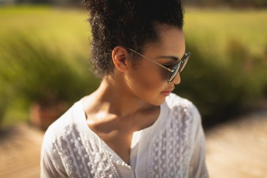 Young mixed-race woman with sunglasses standing in her backyard