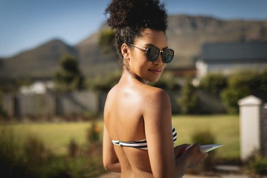 Young mixed-race woman with sunglasses looking at camera