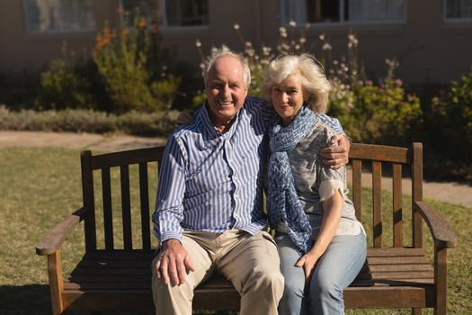 Senior couple sitting with arm around in the park