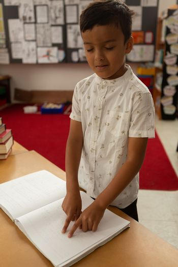 Blind schoolboy reading a braille book in classroom