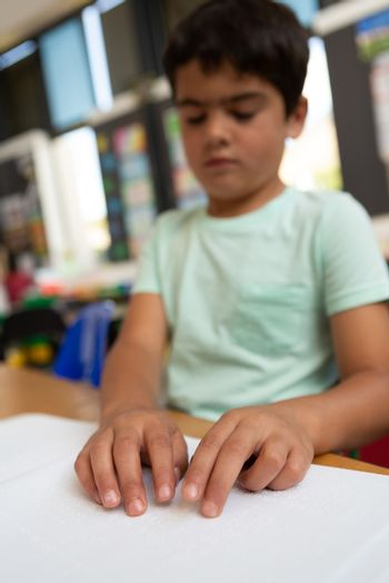Blind schoolboy reading a braille book in the classroom