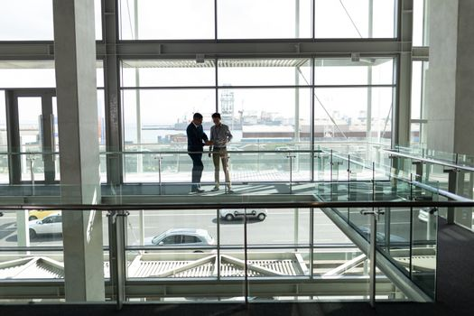 Front distant view of two businessman looking down a digital tablet at the first floor of office
