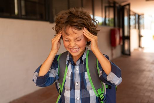 Irritated schoolboy standing in the corridor