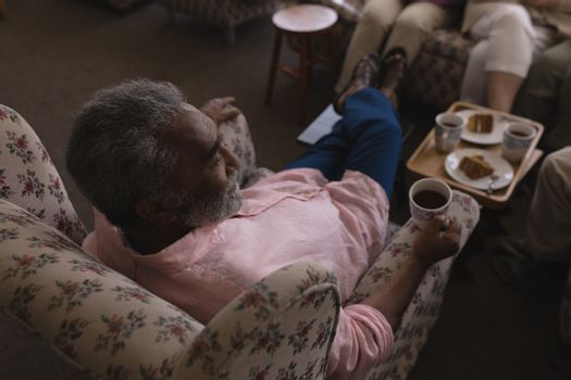 High angle view of senior man having black coffee in living room and sitting on sofa  at home