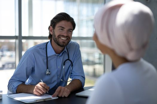 Disabled mixed-race woman and Caucasian male doctor interacting with each other