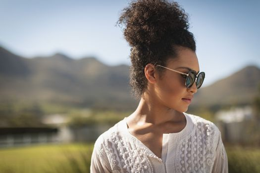 Young mixed-race woman with sunglasses looking away