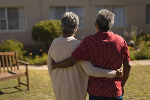 Senior couple standing with arm around in the park