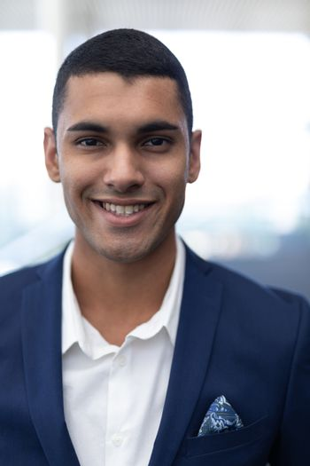 Young mixed-race businessman standing in modern office