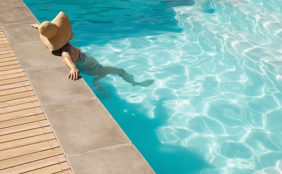 Young mixed-race woman with hat leaning on edge of pool