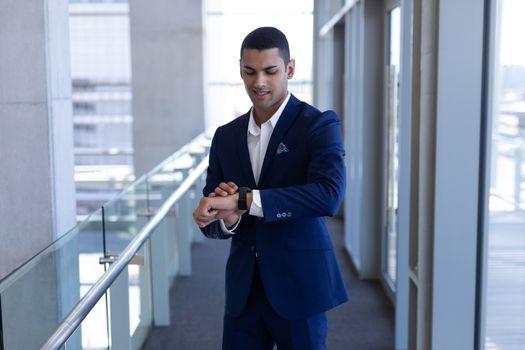 Mixed-race businessman using smartwatch in modern office