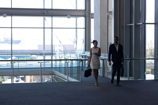 Mixed-race business people walking together in modern office