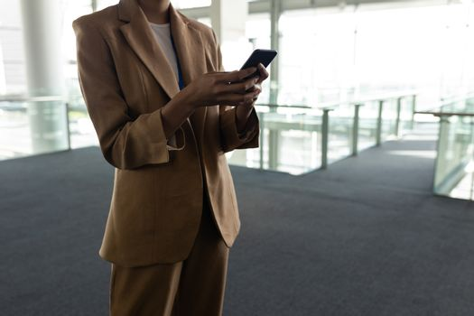 Mixed-race businesswoman using mobile phone in office lobby