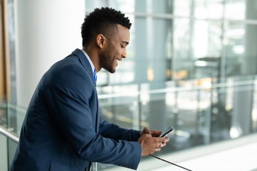 Mixed-race businessman using mobile phone in modern office