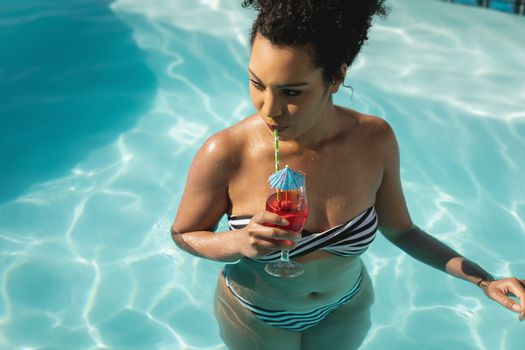 Young mixed-race woman drinking cocktail in swimming pool