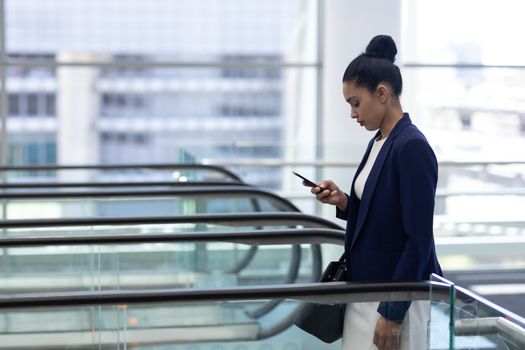 Young mixed-race businessman using mobile phone on escalator